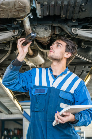 exhaust system: Young male mechanic holding flashlight while examining exhaust system of car in garage