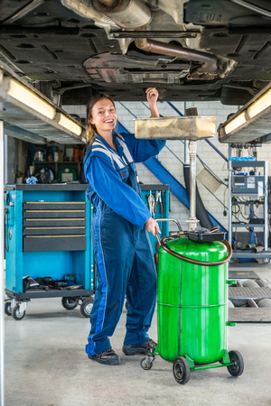 hydraulic lift: Full length portrait of smiling female mechanic repairing car on hydraulic lift in garage