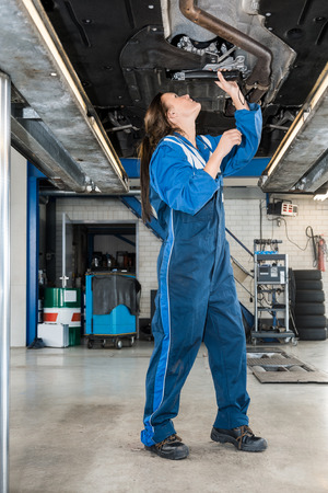 hydraulic lift: Full length of female mechanic repairing car on hydraulic lift in automobile shop Stock Photo