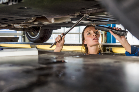 hydraulic lift: Young female mechanic with flashlight repairing car on hydraulic lift in automobile shop Stock Photo