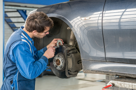 brake disc: Young male car mechanic examining brake disc with caliper in garage