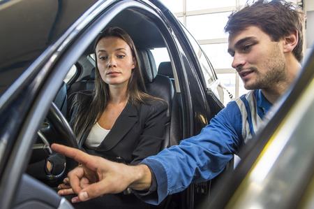 aftersales: A mechanic in overalls explaining and instructing a customer, who has just bought a new car at a garage, as part of the after sales and service program