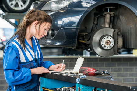 to maintain: Young female mechanic making notes with car in background at garage