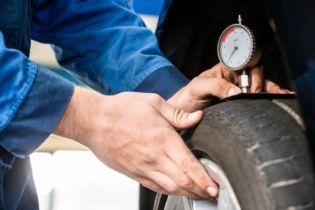 depth gauge: Hands of male mechanic pressing gauge into tire tread to measure its depth at garage