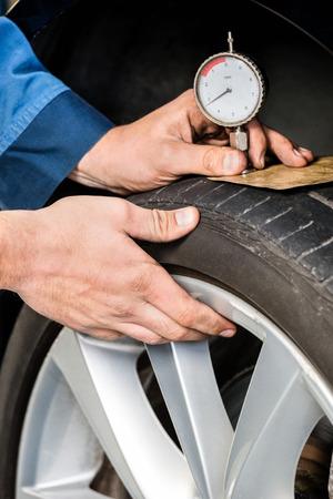 depth gauge: Closeup of male mechanic pressing gauge into tire tread to measure its depth at garage