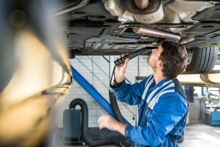exhaust system: Male mechanic with flashlight examining under the car at repair garage