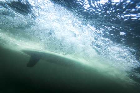 downstream: surfer seen from underwater, moving at high speed with a lot of air bubbles