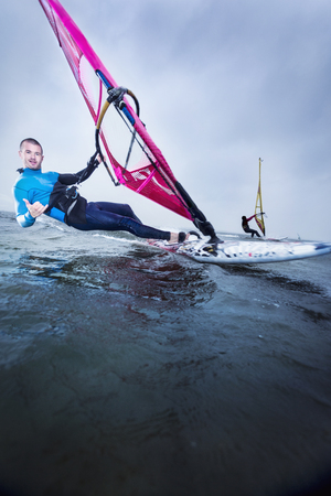 handsign: windsurfer at speed with a smile and a greeting sign