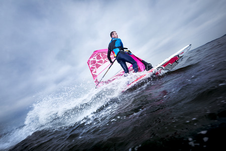 planing: A windsurfer tilts the rig and carves the board to perform a planing or jibe Stock Photo