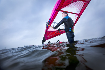 air pressure: professional windsurfer waiting for the right wind in the middle of a big lake