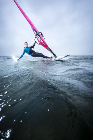 downstream: windsurfer hanging in the strong wind, gliding over the flat water