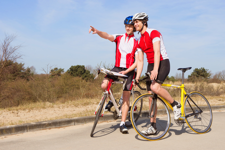 Two cyclists, standing over their bicycles looking ahead at the road to take Stock Photo
