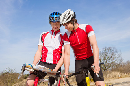 Two cyclists looking at a map for directions, stading over their bicycles photo