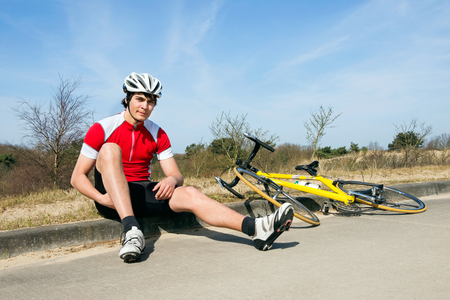 Cyclist in pain sitting on the curb, with his racing bicycle next to him photo