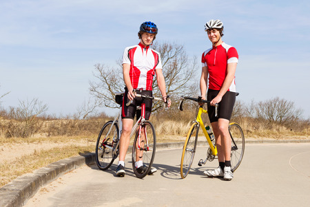 Two cyclists posing with their bicycles photo