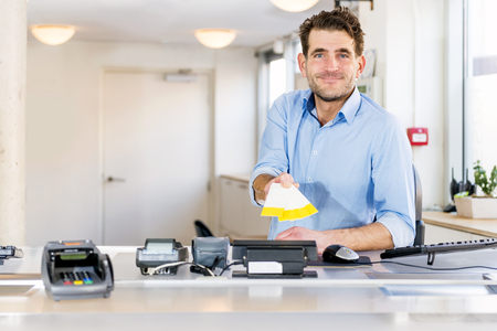 Friendly sales clerk handing over tickets for an event, sitting behind a counter at a ticket booth, smiling. Stock Photo