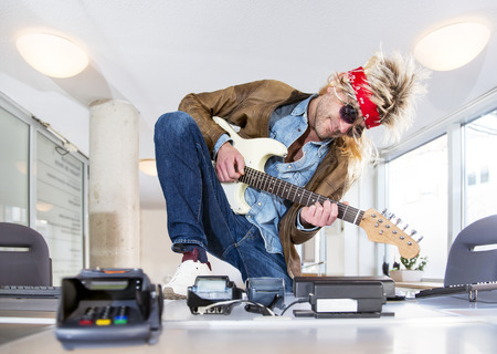 Rockstar at a ticket booth playing a guitar, selling tickets for a rock event or concert at a theater Stock Photo