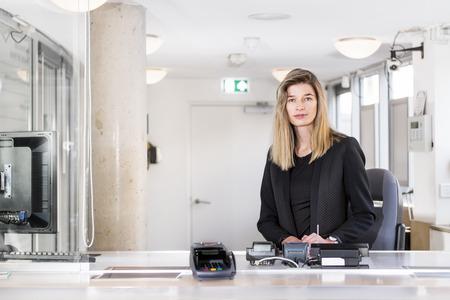 Sales Frau, in noblen schwarzen gekleidet, sitzen hinter dem Tresen einer Kasse in einem Büro
