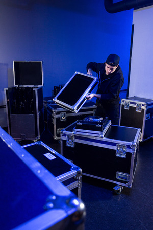 Roadie che disimballa un tavolo da mixaggio per un dj su un flightcase, in preparazione di un evento in una sala da concerto