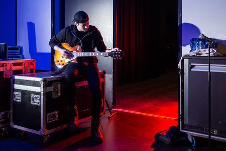 Roadie stemt een gitaar af voor de gitarist naast de ingang van het podium, zittend op een flightcase Stockfoto