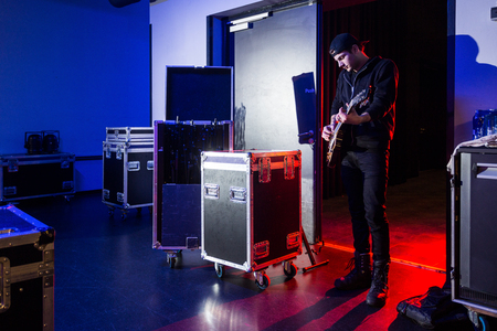 estuches: Roadie playing guitar backstage, standing near the stage entrance, surrounded by flight cases, containing equipment. Foto de archivo