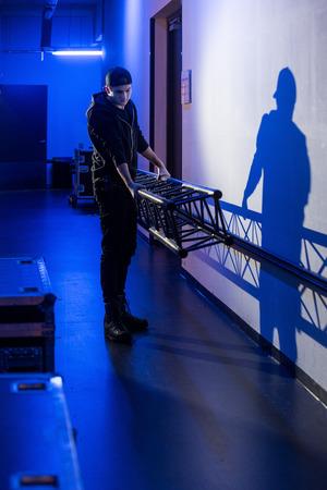 Roadie che porta un grande traliccio sul palco, proiettando un'ombra sul muro,