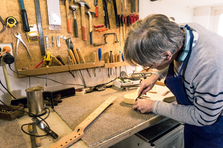 Luthier carefully filing and shaping the neckpocket of an electric guitar