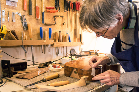 making music: Instrument maker masking a guitar with tape during the construction process, before drilling a hole Stock Photo