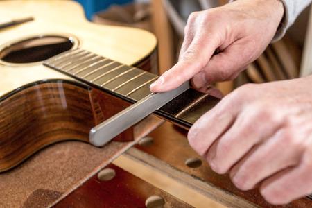 Närbild på händerna på en instrumenttillverkare, arkivering av en akustisk gitarr Stockfoto