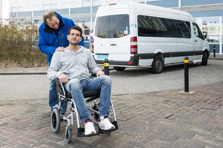 Gehandicapte man in een rolstoel en zijn verpleger wordt afgezet bij een ziekenhuis door een rolstoel taxi