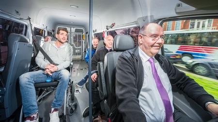 Groep mensen, reizen in een minibus met een gehandicapte persoon in een rolstoel, omringd door een aantal anderen Stockfoto