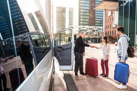 Conducteur d'une minifourgonnette d'aéroport, saluant ses passagers avec leurs bagages sur le trottoir d'un quartier moderne des affaires de la ville Banque d'images - 74738475