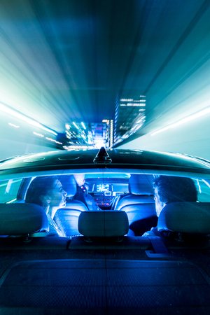 speed car: Car, driving through a tunnel, towards a big city, with office buildings, and towers, with people in the back seet and a driver, seen from the bonnet of the car, through the rear window. Lights flashing by,