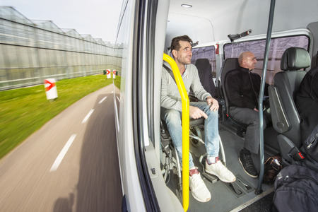 Disabled person, sitting in a wheel chair on the road as passenger in a modified taxi bus, taking a tour through the country side Standard-Bild