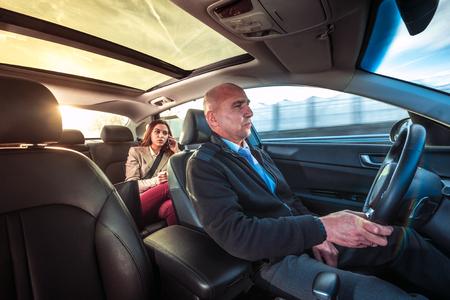 Professionele chauffeur, een taxi chauffeur, het besturen van een vrouw naar haar bestemming.