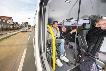tinted: A modified taxi van, carrying a group of people and a disabled man in a wheel chair, driving through a village on a sight seeing tour