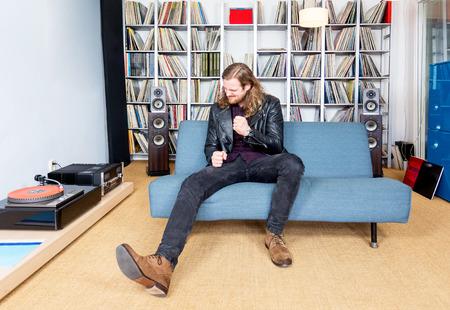 Langhaariger Mann intensiv ejoying Rock-Musik aus Vinyl lange spielen Rekord, auf seinem Sofa
