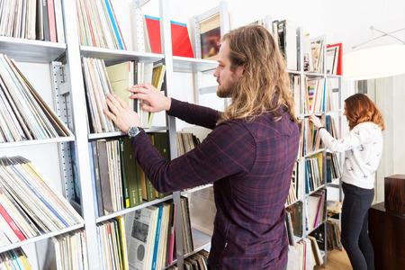 ein paar Blättern durch Racks von Vinyl-Schallplatten in ihrer lp Sammlung Standard-Bild