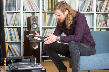 long haired man looking at the track list on a vinyl long playing record to put on the turntable Foto de archivo