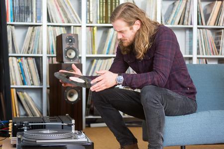 Langharige man kijkt naar de tracklist op een vinyl lange speelrecord om de draaitafel aan te zetten Stockfoto
