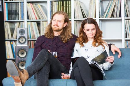ein paar entspannende toghether auf einer couch, lese und hört musik