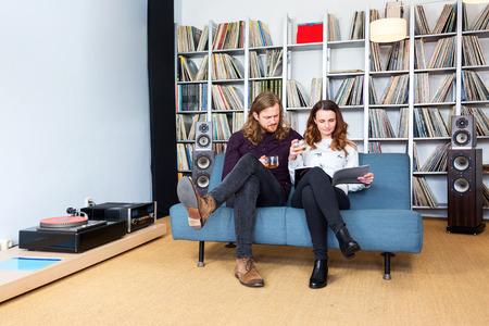 Ein paar sitzen auf dem sofa lese ein magazin zusammen, während musik hören Standard-Bild