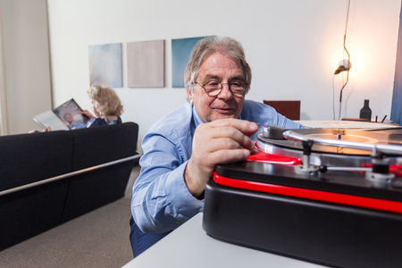 genre: an elderly man carefully placing the needle on a vinyl record