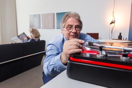 Ein älterer Mann Platzieren sorgfältig die Nadel auf einer Schallplatte