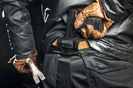 Kriminell, mit einem schwarzen Lederstück, schwarzen Hosen und Lederhandschuhen, hielt eine Krähenstange und griff nach einer verdeckten Pistole, die er hinten in seiner Hose verstaut hatte.