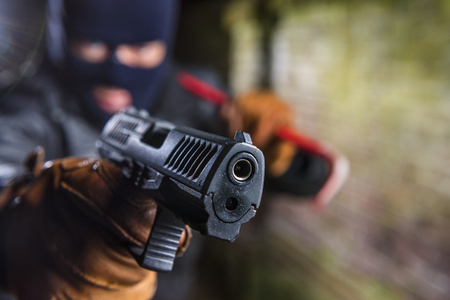 Robber working at night wearing a balaclava and pointing a gun, while holding a crowbar in his hand. Stock Photo