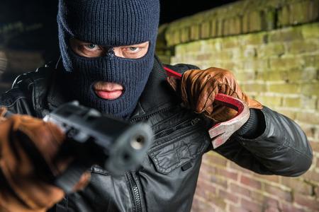 Gangster Holding Crowbar beim Zeigen mit Pistole in der Nacht