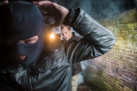 Special Agent nimmt Criminal fest, richtet eine Pistole und eine Taschenlampe auf ihn und befiehlt ihm, seine Hände hochzulegen