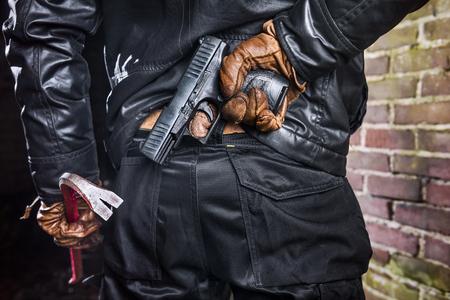 Dieb, der bewaffnet und gefährlich ist, mit einer Brechstange und Pistole hinter seinem Rücken