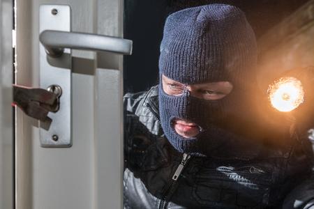 Einbrecher-Holding-Taschenlampe bei dem Versuch, Fensterschloss zu brechen